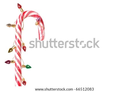 A Single Candy Cane Wrapped in Tiny Christmas Lights with Copy Space - stock photo