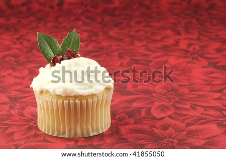 A single Christmas cupcake with white frosting, holly leaves and cranberries, isolated on red Christmas background, horizontal with lots of copy space, selective focus - stock photo