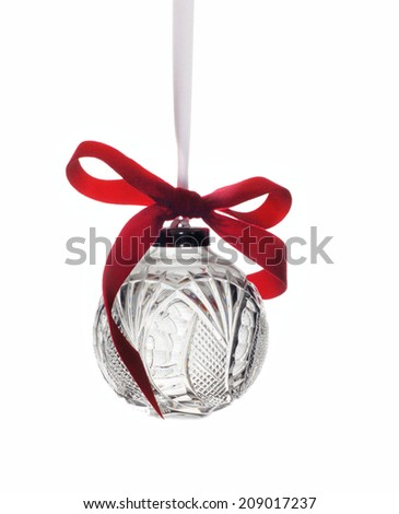 A single crystal Christmas ornament isolated on white. This is a  round, clear waterford crystal with lovely designs cut into it. Hanging from a white ribbon with a bright red bow attached.