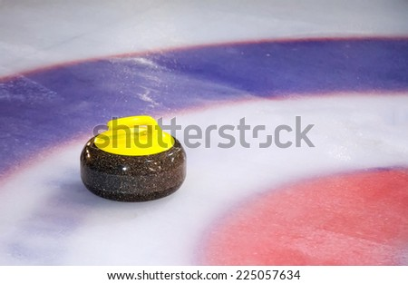 A single curling stone on the ice of a curling rink - stock photo
