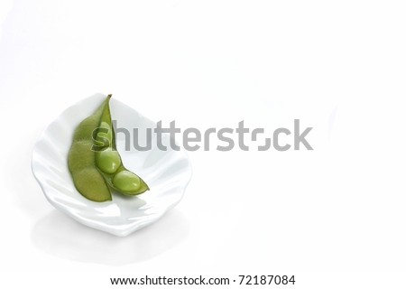 A Single Edamame Soybean Pod, Open to Expose the Soybeans inside, Sitting on a White Plate, With room for Text - stock photo