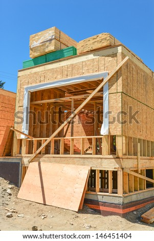 A single family home under construction. The house has been framed and covered in plywood. Stacks of 2x4 boards on the top.