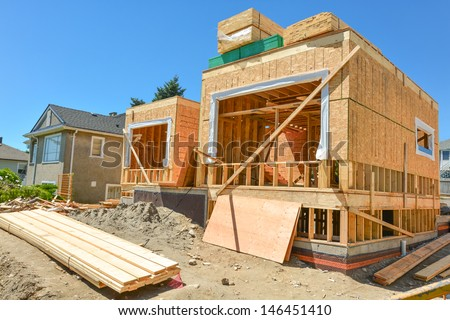 A single family home under construction. The house has been framed and covered in plywood. Stacks of board timber in front and stack of 2x4 boards on the top. - stock photo