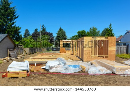 A single family home under construction with tree and blue sky background. - stock photo