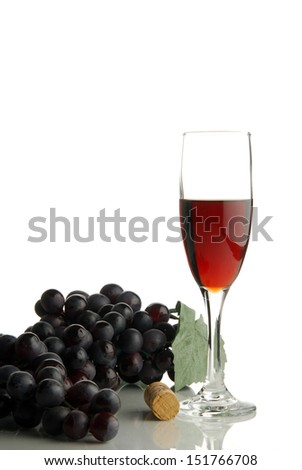 A single glass of red wine beside grapes