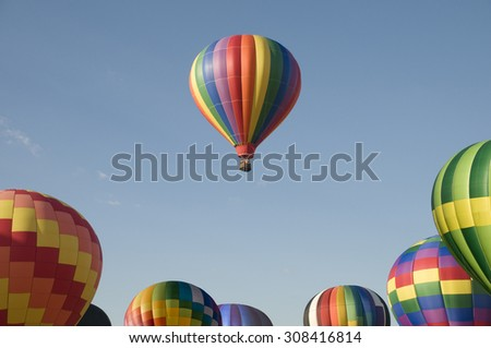A single hot-air balloon floating above others at a balloon festival - stock photo