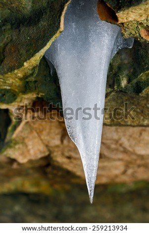 A single icicle catches the light as it hangs from a colorful stone cliff in Indiana. - stock photo