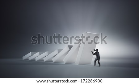 A single man trying to stop collapsing domino pieces - stock photo
