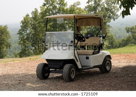 A single new golf cart standing in readiness at a mountain top golf course