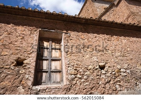 A single, old wooden, window in a stone wall of a house in Alcalali, Spain.