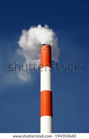 A single red and white striped smoke stack with smoke blowing into a blue sky. - stock photo