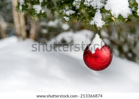 A single red Christmas ball decoration is hanging off a Christmas tree outside partially covered in snow.  Room for copy space.  - stock photo