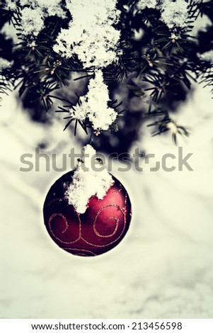 A single red Christmas ball decoration is hanging off a spruce tree outside partially covered in snow.  Room for copy space. Filtered for a retro vintage look.  - stock photo
