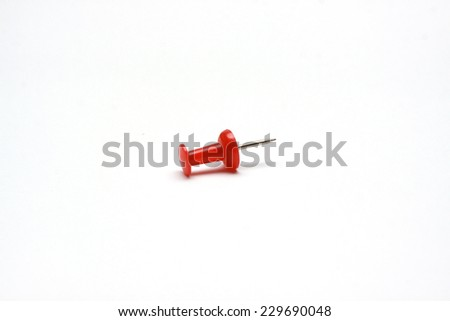 A single red push pin on a white background - stock photo