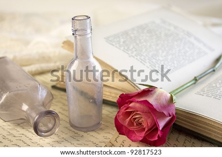 A single red rose laying on top of an opened vintage book with a couple of vintage apothecary bottles. - stock photo