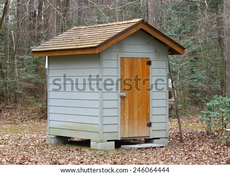A single small storage shed outside among the forest on a winter day - stock photo