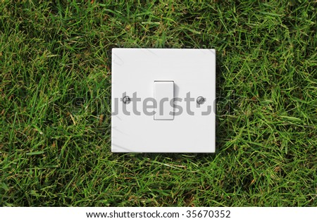 A single square white light switch set on green grass. representing the use of green energy. - stock photo