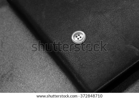 A single white button on black leather wallet - stock photo
