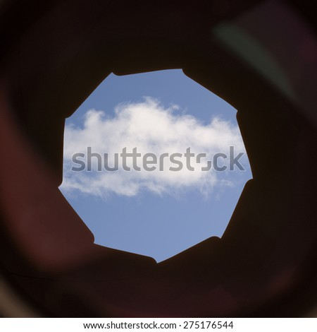 A single white cloud on a blue sky seen through the lens and aperture of a camera. Conceptual image of view on cloud computing, digital communication and storage. - stock photo