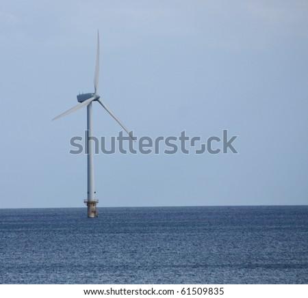 A Single Wind Turbine Tower Standing in the Sea.