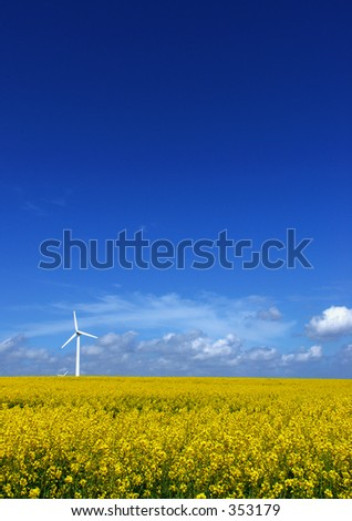 A single windturbine in a rapeseed field and a very blue sky - stock photo