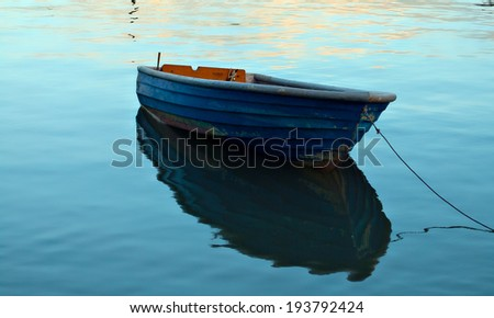 A single wooden boat on the water. - stock photo