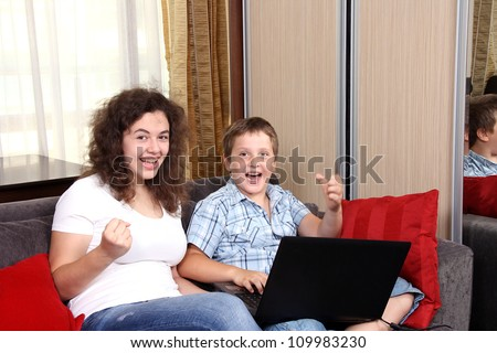 A sister and a brother with a laptop - stock photo