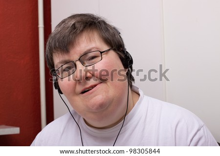 a sitting mentally disabled woman is listening to music - stock photo