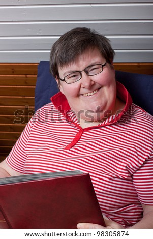 a sitting mentally disabled woman reads and smiles - stock photo