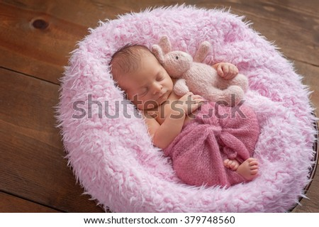 A six day old newborn baby girl sleeping in a round, wooden bowl on pink faux fur. She is swaddled with a berry colored mohair wrap and holding a stuffed toy bunny rabbit. - stock photo