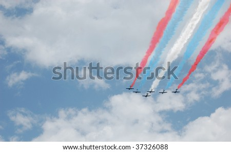 A six plane formation with red, white, and blue smoke trails