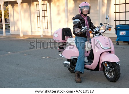 a sixty year old biker stopping on the street in her pink scooter