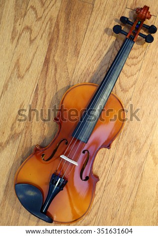 A 3/4 size Violin lays on a hard wood background with beautiful light and shadows for a unique view. Violins are part of the music world, some are worth millions of dollars. - stock photo