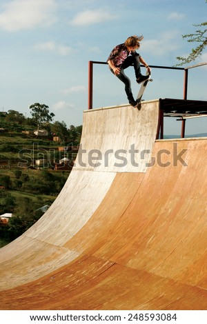 A skateboarder executes a radical move on a wooden half-pipe in Inanda Valley, KwaZulu-Natal, South Africa. - stock photo