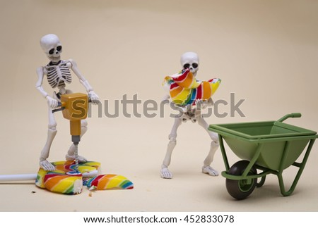 A skeleton breaking and moving lollipop  - stock photo