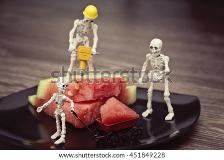 A skeleton cutting watermelon with jackhammer