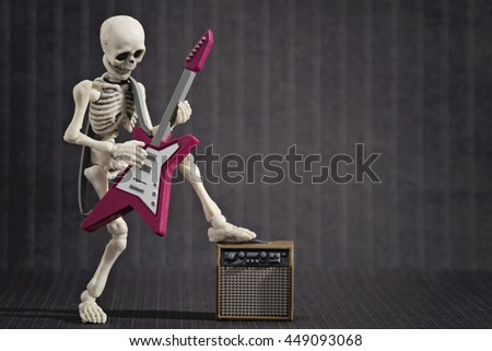 A Skeleton playing his electric guitar - stock photo
