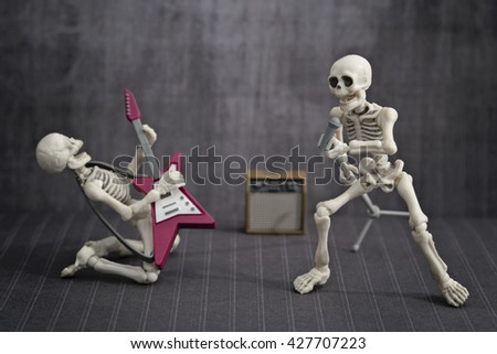 A skeleton playing rock guitar while the other singing
