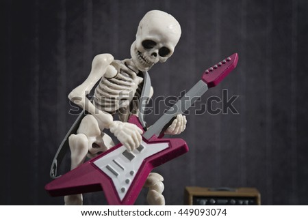A Skeleton playing rock music with his electric guitar - stock photo