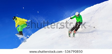 A ski driver and a snowboarder on the piste in Alps by Lech, Austria.