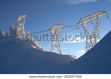 A skier and snowboarder hike up a mountain at Stevens Pass, Washington under the power lines - stock photo