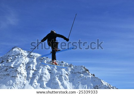 a skier dressed in black performing a very high jump with a snow covered mountain in the background