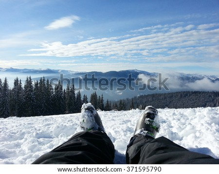 A skier sitting on a slope looking at landscape - stock photo