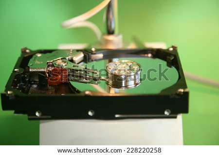A skilled Computer Technician examines a Computer Hard Drive under a Microscope looking for flaws, scratches in the disc, and other issues to repair or replace. Computer Hard Drives are important - stock photo