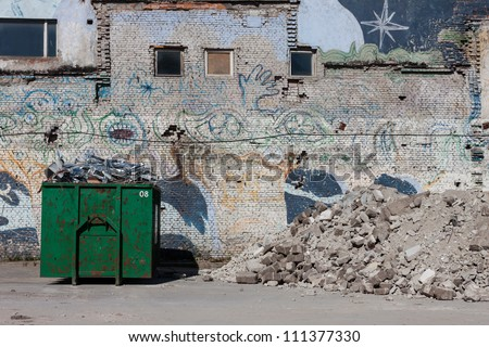 A skip full of rubble outside a construction site with waist container - stock photo