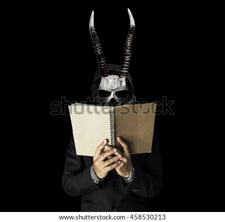 A skull guy with horns in black suit reading notebook, on black dark background