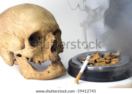 a skull with cigarette, smoke and ashes - stock photo