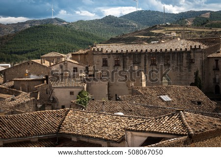 A skyline of an old Spanish town with red clay roofs, green field and mountains