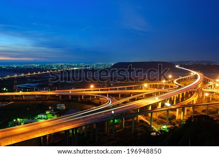 A skyline view of lit up intersecting freeways. - stock photo