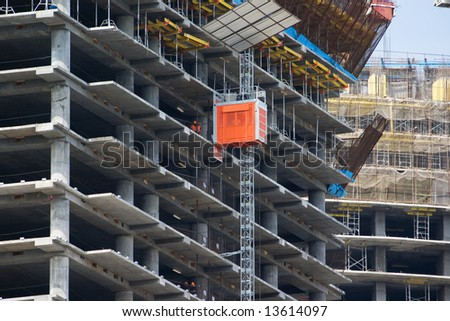 A skyscraper in construction phase with construction equipment on it - stock photo